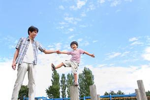 公園の遊具でバランスをとる少年と父の写真素材 [FYI03215701]