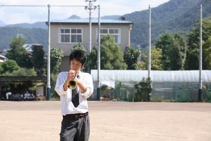 校庭でトランペットを吹く男子学生の写真素材 [FYI03215732]