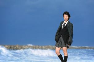 海のテトラポットに立つ女子学生の写真素材 [FYI03215733]