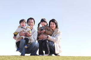 芝生の上で笑う家族の写真素材 [FYI03215740]