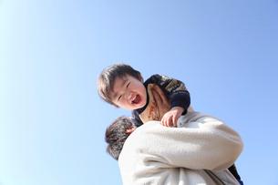 青空の下で父親に抱かれる男の子の写真素材 [FYI03215747]