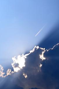 雲間からの日差しと飛行機雲の写真素材 [FYI03215749]