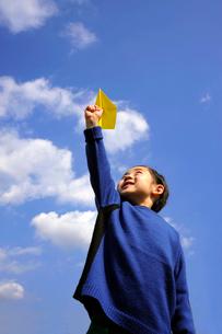 黄色の紙飛行機を飛ばす男の子の写真素材 [FYI03215856]