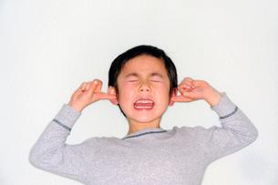 両手で耳をふさぐ少年の写真素材 [FYI03215876]