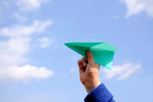 紙飛行機(緑色)と少年の手の写真素材 [FYI03215884]