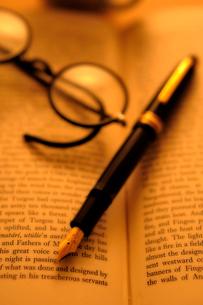 洋書の上の万年筆と眼鏡の写真素材 [FYI03215922]