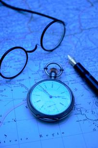 地図の上の懐中時計と万年筆と眼鏡の写真素材 [FYI03215927]