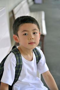 駅のベンチに座る少年の写真素材 [FYI03215937]