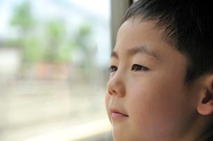 車窓から外を見る少年の写真素材 [FYI03215940]