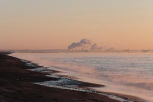 気嵐立つ波打ち際と工場の煙突の写真素材 [FYI03217871]