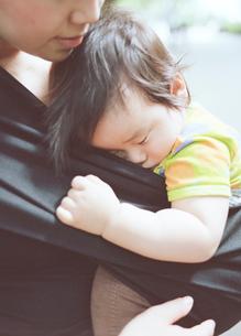 母親のだっこ紐のなかで眠る子供の写真素材 [FYI03219059]