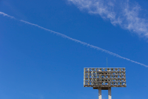 青空と競技場の照明灯と飛行機雲の写真素材 [FYI03219683]