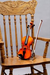 アームチェアに乗せたバイオリンの写真素材 [FYI03219906]