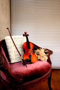 アームチェアにバイオリン、造花,楽譜を乗せたの写真素材 [FYI03219924]