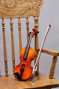 アームチェアに乗せたバイオリンの写真素材 [FYI03219932]