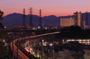 流れる電車の光跡と暮れゆく街の写真素材 [FYI03224390]