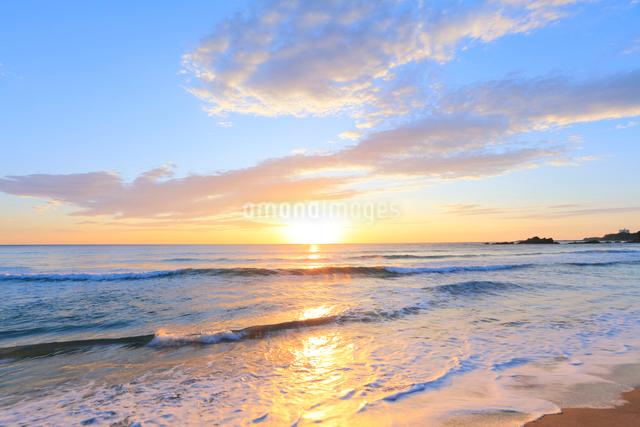 浜辺によせる波と朝日の写真素材 [FYI03224604]