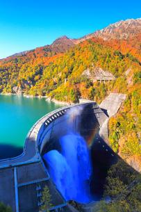秋の立山・黒部ダム観光放水に虹と快晴の空に紅葉の写真素材 [FYI03224886]