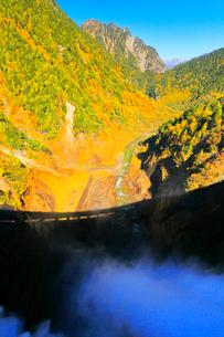秋の立山・黒部ダム観光放水と快晴の空に山並みの写真素材 [FYI03224887]