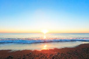 元日の浜辺に寄せる波と初日の出の写真素材 [FYI03224914]