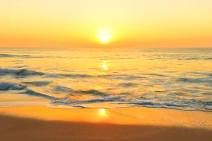 浜辺に寄せる波と朝日の写真素材 [FYI03224931]
