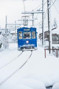 雪の中を走る万葉線1の写真素材 [FYI03225438]