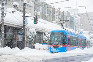 雪の中を走る万葉線ドラえもんトラム3の写真素材 [FYI03225442]