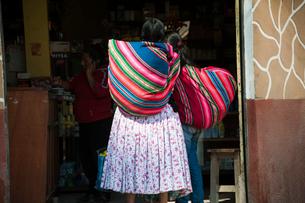 ボリビア先住民アイマラ族のカラフルな風呂敷アグアヨを担ぐ女性の写真素材 [FYI03225628]