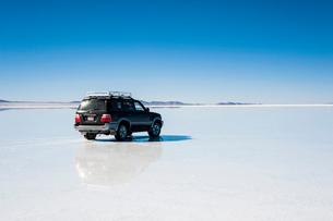 鏡張りのウユニ塩湖と車の写真素材 [FYI03225943]