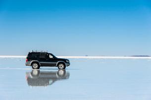 鏡張りのウユニ塩湖と車の写真素材 [FYI03225945]