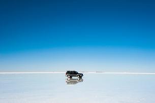 鏡張りのウユニ塩湖と車の写真素材 [FYI03225948]