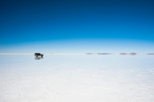 鏡張りのウユニ塩湖と車の写真素材 [FYI03225950]
