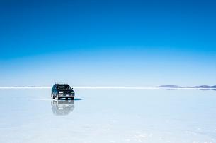 鏡張りのウユニ塩湖と車の写真素材 [FYI03225951]