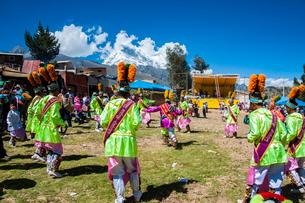 カーニバルの民族舞踏を踊るダンサーとアンデス山脈の写真素材 [FYI03226264]