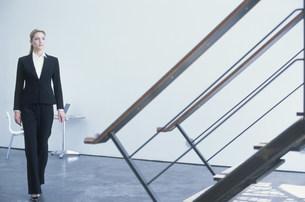 階段越しの壁際から歩いてくるスーツ姿の女性の写真素材 [FYI03228727]