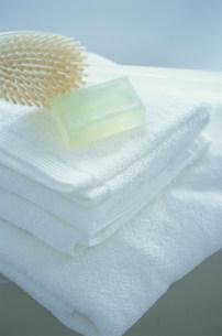 畳まれたタオルの上に置かれた石鹸とブラシの写真素材 [FYI03228758]