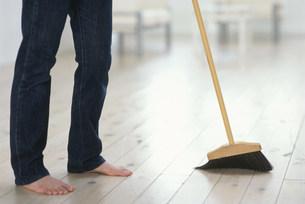 床掃除をしている足元とホウキの写真素材 [FYI03228785]