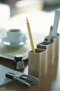 デスク上の万年筆やホチキス等の文具とコーヒーの写真素材 [FYI03228820]
