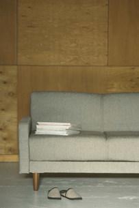 ソファの上に重ねられた雑誌とスリッパの写真素材 [FYI03228822]