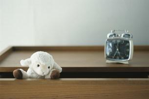 棚の上の時計と引出しから顔を出したヌイグルミの写真素材 [FYI03228826]