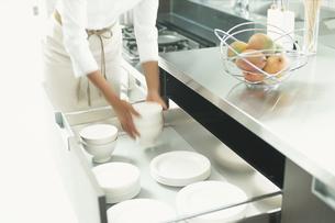 キッチンの引出しに食器をしまう女性の写真素材 [FYI03229016]