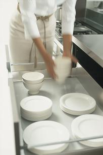 キッチンで白い食器をしまう女性の写真素材 [FYI03229027]