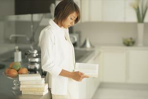 キッチンで洋書を読む女性の写真素材 [FYI03229033]