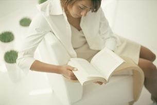 白い椅子に座って洋書を読む女性の写真素材 [FYI03229037]
