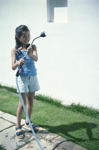 庭で水をまく女の子の写真素材 [FYI03229046]