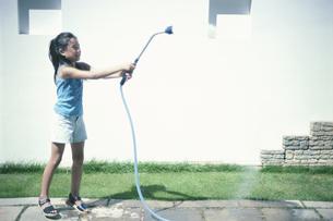 庭で水を撒く女の子の写真素材 [FYI03229053]
