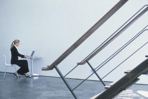 階段越しの壁際に座りパソコンを見るスーツの女性の写真素材 [FYI03229109]