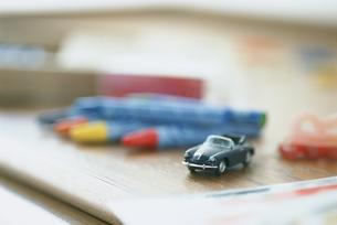 机の上のミニカーとクレヨンの写真素材 [FYI03229111]