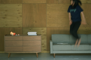 部屋でジャンプする人の写真素材 [FYI03229137]