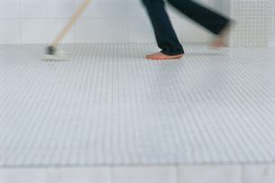 タイルにモップをかける人の足の写真素材 [FYI03229139]